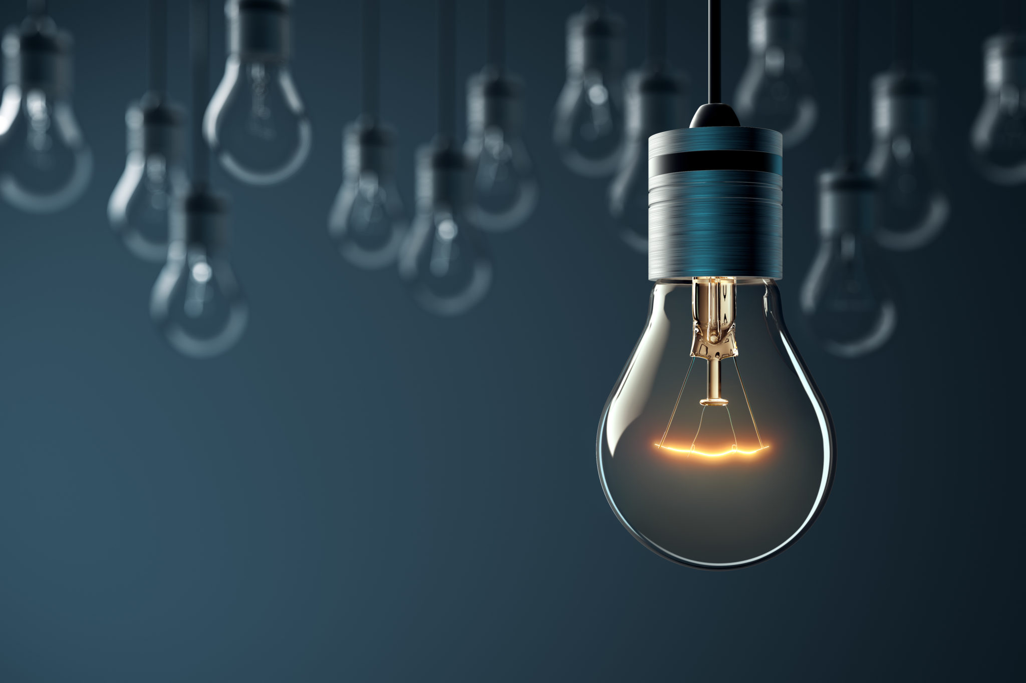 Hanging glowing light bulb on blue background